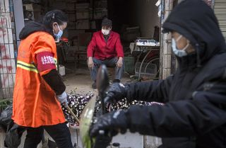 This photo shows a masked vendor and customers of his wares in an alley in Wuhan, China, on January 31, 2020.
