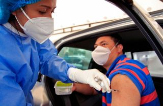 A man receives a dose of a COVID-19 vaccine at a drive-through distribution site in Bogota, Colombia, on April 11, 2021.