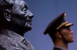 A bust of former Chinese leader Deng Xiaoping looks out at a member of China's People's Liberation Army.
