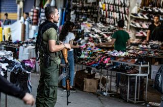 A member of the Kurdish Internal Security Police Force of Asayish stands guard at a market in the northeastern Syrian city of Qamishli on Aug. 5, 2019.