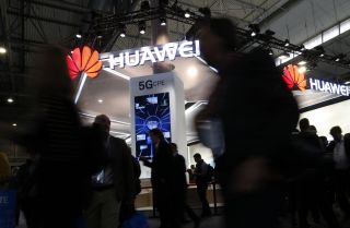 Conference attendees walk past a booth for Chinese telecommunications company at the Mobile World Congress in Barcelona, Spain. Huawei has not drawn the concern in Europe that it has in the United States.