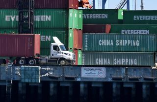 Dock workers unload shipping containers with goods imported from China and elsewhere at the Port of Long Beach in Los Angeles.