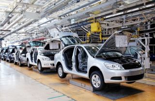 Cars sit on an assembly line.