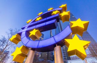 A statue of the euro logo is seen in front of the European Central Bank building in Frankfurt, Germany, on March 27, 2020.