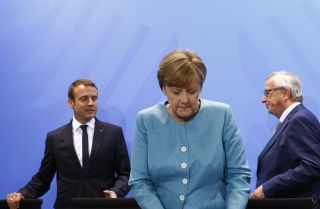 German Chancellor Angela Merkel, French President Emmanuel Macron and European Commission President Jean-Claude Juncker gather for a press conference after a June 29 meeting of EU leaders in Berlin.