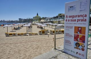 A large billboard alerts beachgoers of COVID-19 safety measures in Praia do Tamariz, a favorite spot for locals and tourists, on July 29, 2020, in Estoril, Portugal.