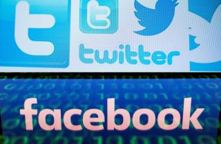 A photo illustration displays Twitter and Facebook's logos on a computer screen.