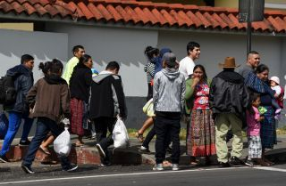 Migrants deported from the United States stand outside an air force base in Guatemala City on Dec. 12, 2019.
