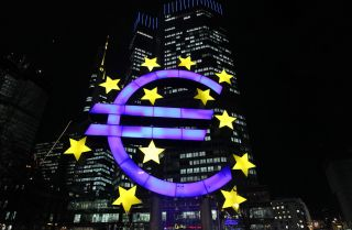 The illuminated sculpture by German artist Ottmar Hoerl's depicting the Euro is seen in front of the European Central Bank.