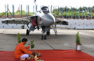 A ceremony, complete with a Hindu priest, marks the commissioning of a new Indian fighter jet in Bangalore.