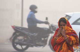 An Indian girl walks with her face covered amid heavy smog in New Delhi on Nov. 13.
