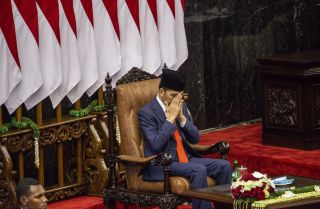 "Indonesian President Joko ""Jokowi"" Widodoprays during hisinauguration for his second termon Oct. 20, 2019, in Jakarta."