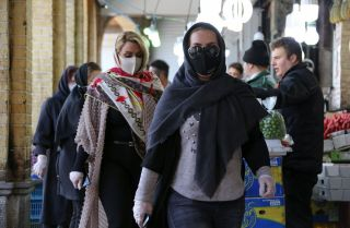 Shoppers wear protective face masks in a bid to prevent the spread of COVID-19 in a market on April 5, 2020, in the Iranian capital of Tehran.