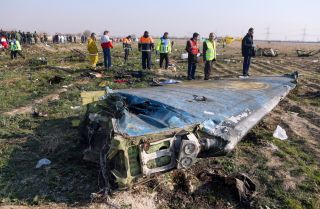 Teams examine the scene of a Ukrainian airliner that crashed being unintentionally targeted by Iranian air defenses shortly after takeoff in Tehran on Jan. 8, 2020.