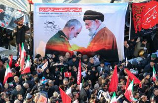 Mourners in Tehran carry a banner featuring Maj. Gen. Qassem Soleimani and Supreme Leader Ayatollah Ali Khamenei during the military leader's funeral procession on Jan. 6.