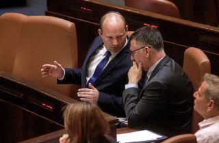 Israeli Prime Minister Naftali Bennett (left) speaks with Justice Minister Gideon Sa'ar in the Knesset on June 16, 2021.