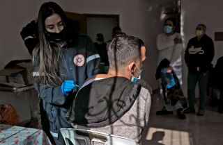 A health worker administers a dose of the Pfizer-BioNtech COVID-19 vaccine at a mobile clinic near Moshav Dalton in northern Israel on Feb. 22, 2021.