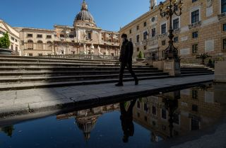 A man wearing a face mask walks in Pretoria square in Palermo, Italy, on March 11, 2020.