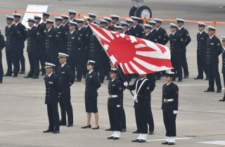 Japanese navy servicemen in Omitama stand with their flag on a runway in anticipation of an upcoming ceremony.