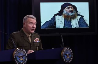 U.S. Marine Corps Gen. Kenneth McKenzie speaks as a picture of Abu Bakr al-Baghdadi is seen during a press briefing Oct. 30, 2019, at the Pentagon in Arlington, Virginia.
