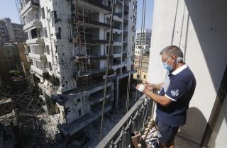 A man looks from the balcony of a building, damaged by the port explosion a day earlier, in Beirut, Lebanon on Aug. 5, 2020.