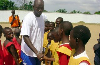 Liberia's star soccer player turned politician George Weah shakes hands with former children soldiers in Monrovia.