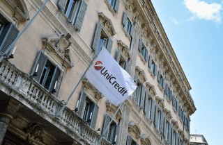 A flag bearing UniCredit's logo is shown in downtown Rome.