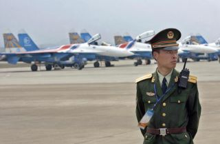 A Chinese officer stands guard before a row of Russian Su-27 'Flankers'. Negotiations over the sale of Russian navy fighter jets to China have broken down. The dispute actually represents a much larger issue -- China's growing expertise at reverse-engineering and copying Russia's military hardware.