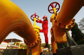 A Chinese worker checks a gas pipe valve at a natural gas plant in southwest China's Sichuan province.