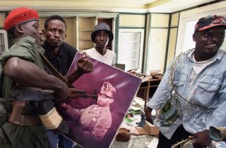 A Congolese rebel alliance soldier surrounded by looters in Kinshasa prods a photograph of ousted Zairean President Mobutu Sese Seko in 1997. African populations are demanding more from their leaders, and not all leaders are prepared to give it.