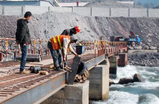 A Chinese engineer supervises workers building a bridge over a river near Muzaffarabad, the capital of Pakistani-administered Kashmir.