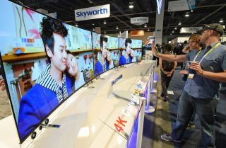 Attendees look at 65-inch Skyworth 4K curved OLED televisions on display at the 2015 International CES at the Las Vegas Convention Center.
