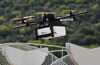 A French Geopost drone hovers, showing a prototype package delivery system in action in France. In the United States, regulations will delay the use of drones in urban environments and home deliveries.