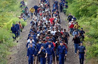 Refugees from various countries walk along railway tracks near the Hungarian town of Szeged.