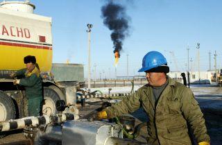 A Kazakh worker unloads oil at a terminal.