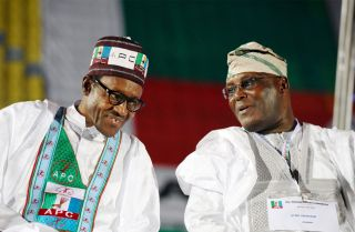Nigerian President Muhammadu Buhari (L) talks with rival politician Atiku Abubakar in Lagos.