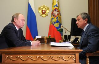 Russian President Vladimir Putin and Igor Sechin (R), CEO of state-controlled Russian oil giant Rosneft, may be at odds in debates over proposals to make state firms pay more funds to the government.