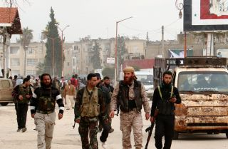 Fighters from a coalition of Islamist forces walk through the Syrian city of Idlib on March 29.