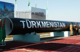 Two workmen stand next to the symbolic first piece of a natural gas pipeline to China outside of Turkmenabat in 2007.