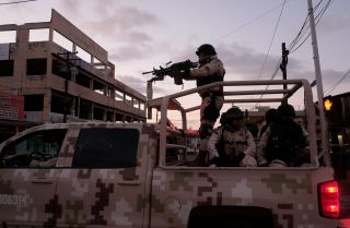 Mexican Soldiers leave the scene of a crime where a man was killed by gun fire in downtown Tijuana.