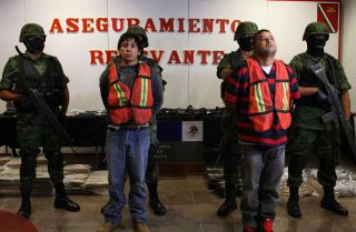 Mexican soldiers escort Oscar Pozos Jimenez (L) and Jose Serna Padilla, an alleged member of the Cartel de Jalisco Nueva Generacion, in Guadalajara on March 18, 2012.