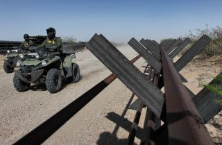 U.S. Border Patrol agents ride ATVs alongside an unfinished portion of a border wall between Ciudad Juarez in Mexico and Santa Teresa in the United States on April 17, 2018.