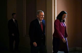 U.S. Senate Majority Leader Mitch McConnell, left, and an aide walk toward the Senate chamber in the U.S. Capitol on Feb. 12, 2018.