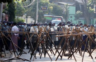 Riot police approach protesters' barricades in an attempt to disperse a March 4, 2021, demonstration in Naypyidaw, Myanmar, against the military coup.