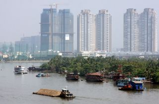New buildings tower above boats on the Saigon river.