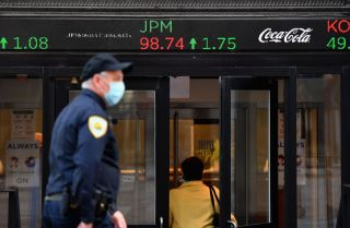 People wearing masks walk by the New York Stock Exchange (NYSE) in lower Manhattan on Oct. 5, 2020, in New York City.