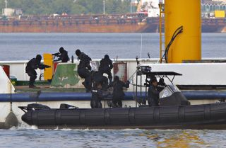 Royal Malaysian Police Special Forces personnel storm a mock hijacked ship during an anti-piracy demonstration exercise June 13, 2007, in Port Klang, Malaysia.