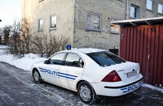 A police car is parked outside of the place where Islamist militants were arrested, suspected of a plot to massacre staff at a Danish newspaper.