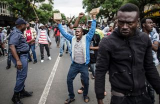 A crowd of Nigerians faces off with South Africans in Pretoria on Feb. 24 while a South African policeman (L) tries to calm them. Populism has taken root in the impoverished and unemployed segments of South African society.