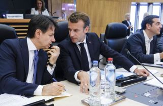 Italian Prime Minister Giuseppe Conte, left, speaks with French President Emmanuel Macron during a summit on migration issues at EU headquarters in Brussels on June 24.